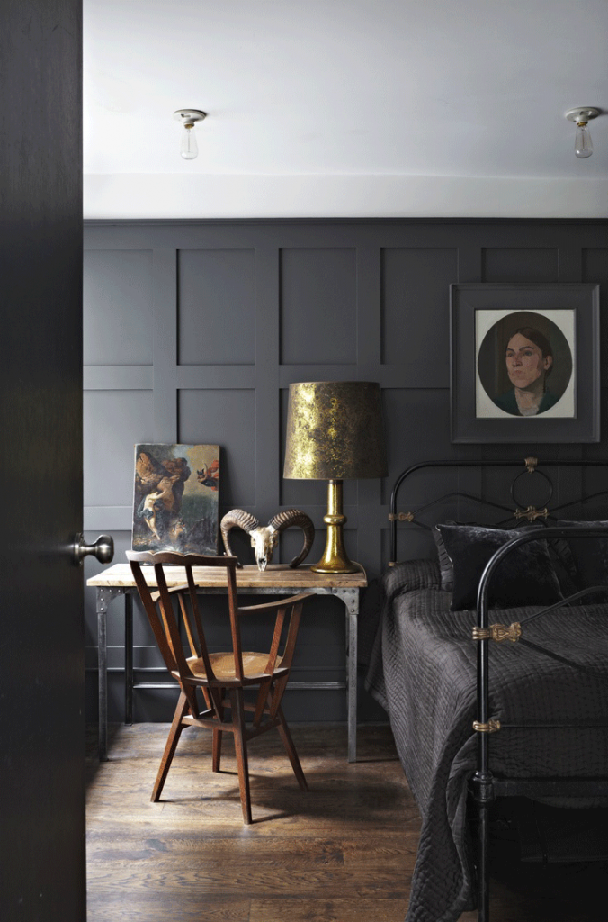 Here the painted paneling sits along side rusticated brass details, exposed light fittings, and wide medium colour timber floorboards to create a cosy, winter bedroom.